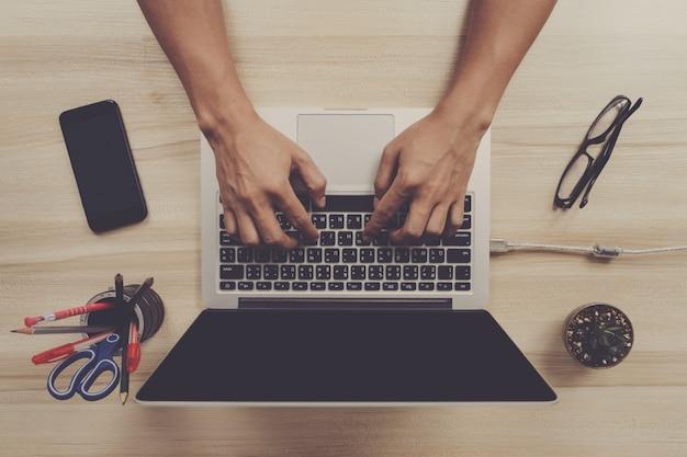 Draufsichtmannhände schreiben auf laptoptastatur mit smartphone und brillen auf arbeitsschreibtisch