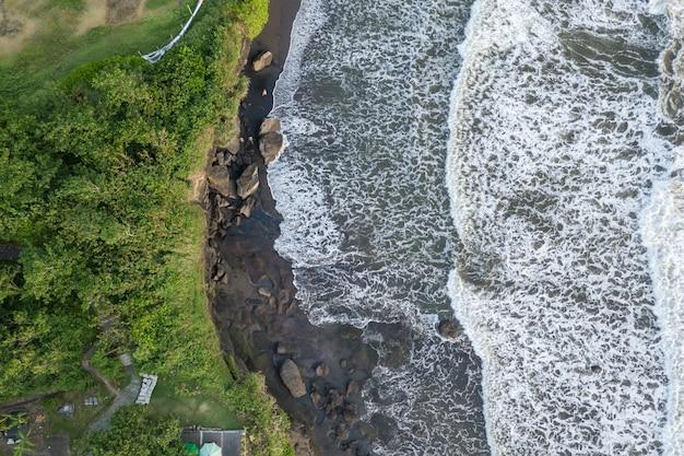 Draufsichtmeerblick mit den wellen, die gegen die felsen brechen