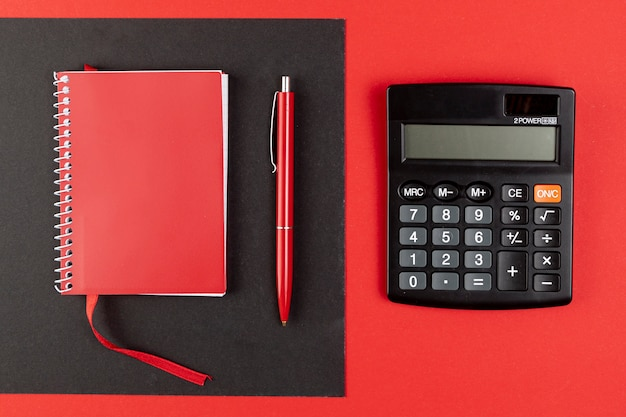 Draufsichtminitaschenrechner nahe bei rotem notizbuch