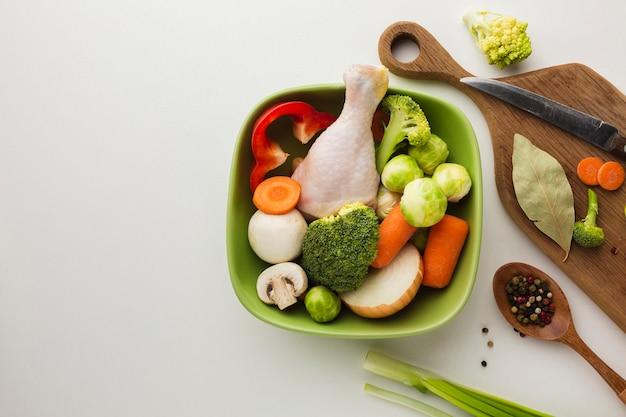 Draufsichtmischung des gemüses auf schneidebrett und in der schüssel mit hühnertrommelstock und löffel mit kopienraum