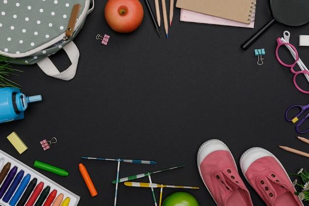 Draufsichtmodell des bildungszubehörs mit rucksack, schülerbüchern, schuhen, buntem wachsmalstift, brille, leerem raum auf tafelhintergrund, bildungskonzept und zurück zur schule