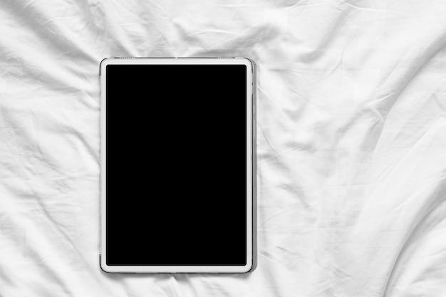 Draufsichtmodell des weißen tablet-pcs mit leerem weißen desktop-bildschirm auf einem gemütlichen weißen bett zu hause