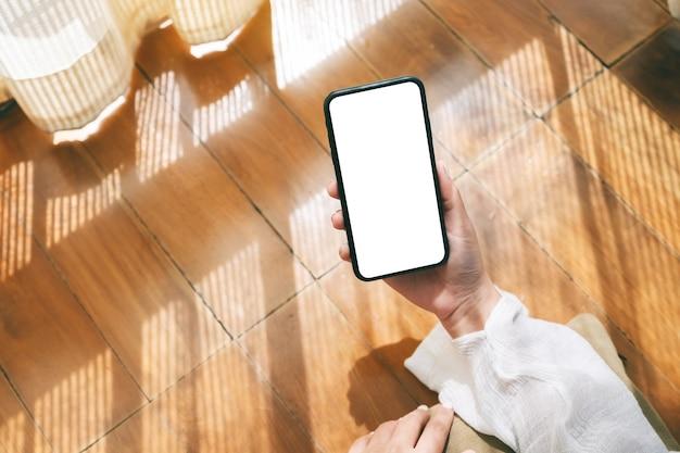 Draufsichtmodell einer frau, die ein schwarzes mobiltelefon mit leerem desktop-bildschirm hält und verwendet, während sie sich entspannt auf den boden legt