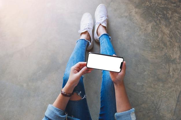 Draufsichtmodell einer frau, die ein schwarzes mobiltelefon mit leerem weißem bildschirm hält, während sie auf dem boden sitzt