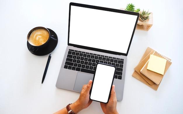 Draufsichtmodell von händen, die ein leeres mobiltelefon mit weißem bildschirm und einen laptop auf dem tisch im büro halten