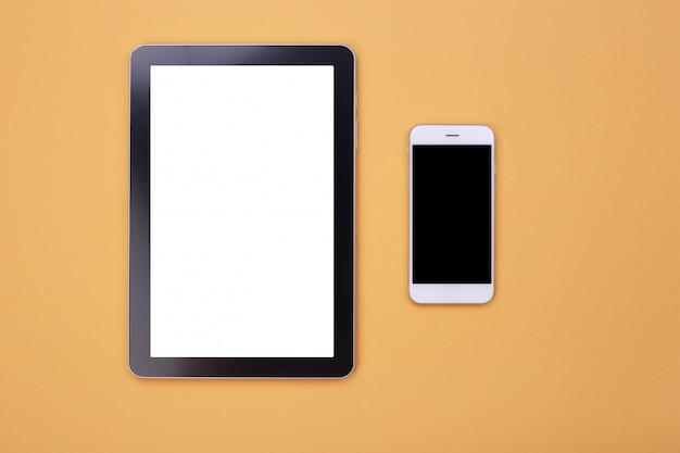 Draufsichtmodelltablette und -smartphone auf orange pastellhintergrund