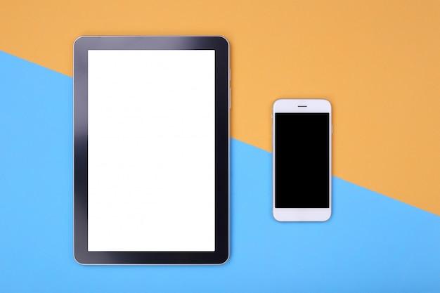Draufsichtmodelltablette und -smartphone auf orange und blauem pastellhintergrund
