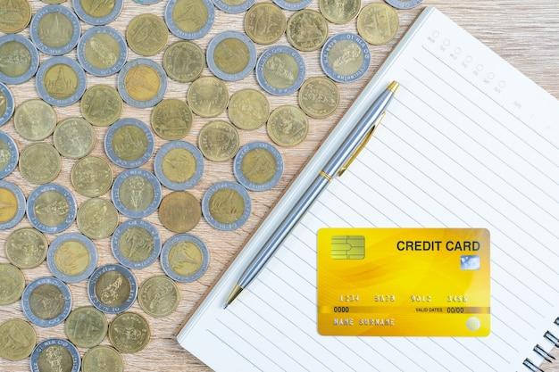 Draufsichtmünzen mit kreditkarte auf holztisch unter verwendung als finanzkonzept