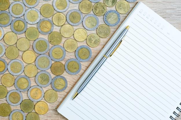 Draufsichtmünzen mit notizblock auf holztisch unter verwendung als finanzkonzept