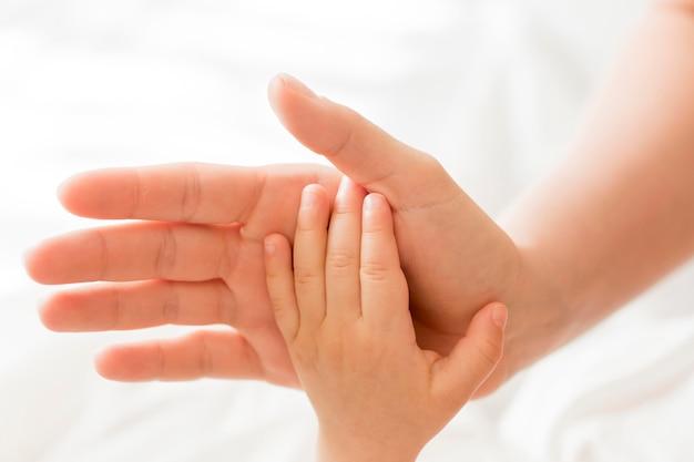 Draufsichtmutter, die babys hand hält