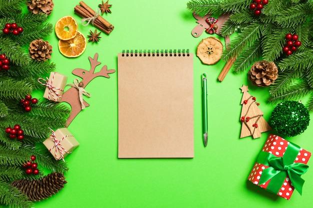 Draufsichtnotizbuch auf grün machte weihnachtsdekorationen. zeit