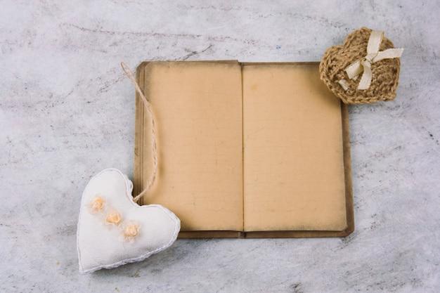 Draufsichtnotizbuch mit altem weinlesepapier und angefüllten spielwarenherzen