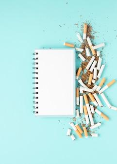 Draufsichtnotizbuch mit stapel von zigaretten