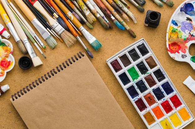 Draufsichtnotizbuch umgeben durch malende elemente