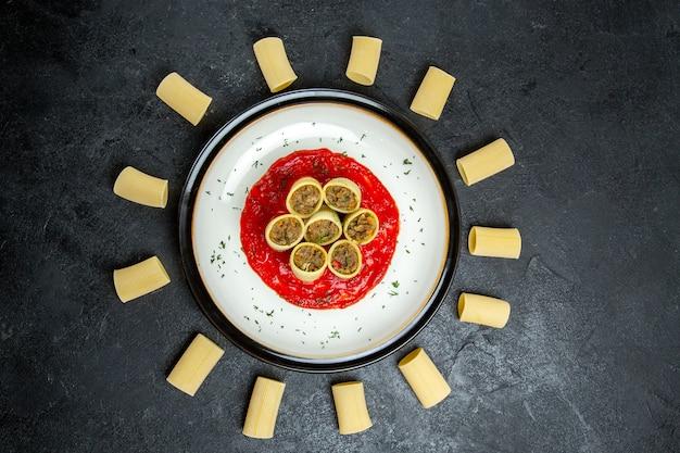 Draufsichtnudeln mit fleisch- und tomatensauce auf grauem hintergrundfleischnahrungsmittelgebäcknudelteig
