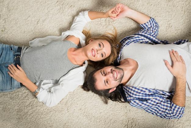 Draufsichtpaarporträt, das auf teppich legt