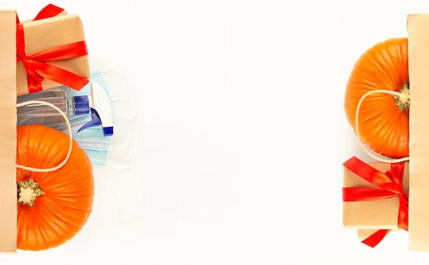 Draufsichtpapiertüte mit frischem kürbis, geschenkboxen und virenschutz. einkaufen für halloween oder thanksgiving. banner. flach liegen. platz kopieren.