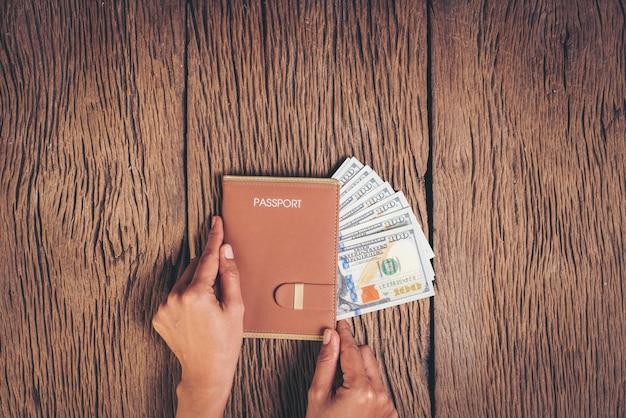 Draufsichtpass mit geld auf hölzernem hintergrund, tourismuskonzept