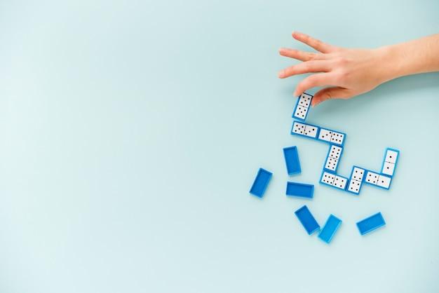 Draufsichtperson, die domino spielt