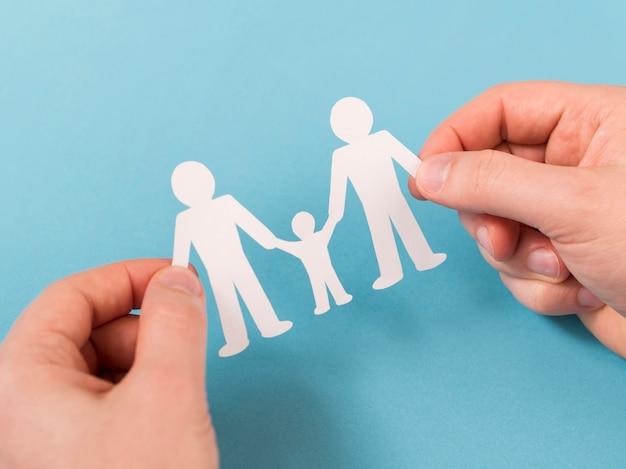 Draufsichtperson, die in händen niedliche papierfamilie hält