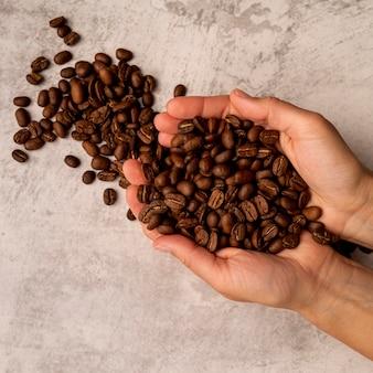 Draufsichtperson, die röstkaffeebohnen hält