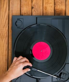 Draufsichtperson, die vinylaufzeichnung in spieler legt