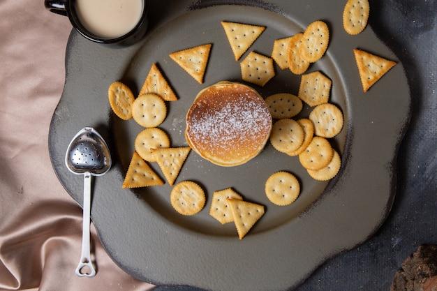 Draufsichtpfannkuchen mit crackern innerhalb grauer platte mit milch knusprigem crackersnackfoto