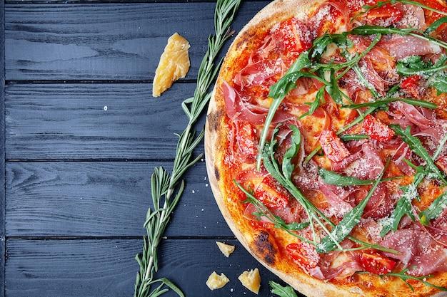 Draufsichtpizza mit jamon, rucola, kirschtomate und käse auf dunklem hölzernem hintergrund. kopieren sie sapce für design. lebensmittelhintergrund. italienische küche. flaches essen