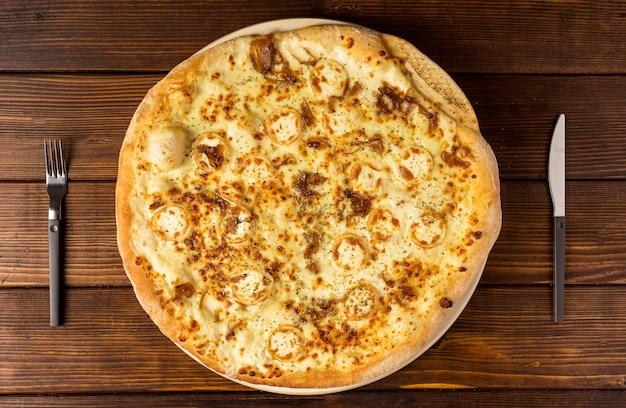 Draufsichtpizza mit käse und besteck
