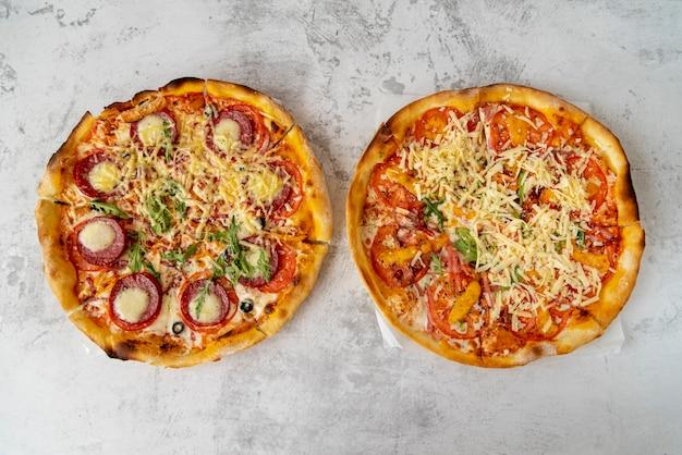 Draufsichtpizzas auf zementhintergrund