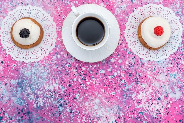 Draufsichtplätzchen mit sahne zusammen mit tasse kaffee auf dem farbigen schreibtischkuchenzuckersüßteig
