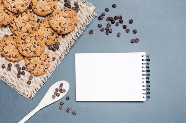 Draufsichtplätzchen mit schokoladensplittern und notizbuch