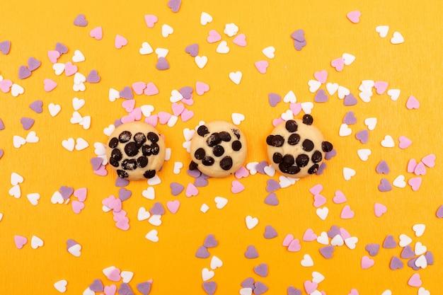 Draufsichtplätzchen mit schokoladenstücken mit herzförmigen dekorationen auf gelber oberfläche