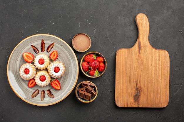 Draufsichtplätzchen und erdbeerplätzchen mit erdbeeren auf weißem teller neben schüsseln mit erdbeerschokolade und schokoladencreme neben dem schneidebrett