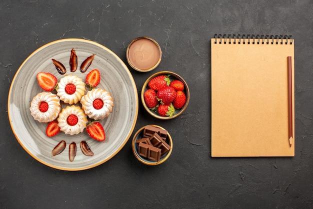 Draufsichtplätzchen und erdbeerplätzchen mit erdbeeren auf weißem teller neben schüsseln mit erdbeerschokolade und schokoladencreme neben notizbuch und bleistift