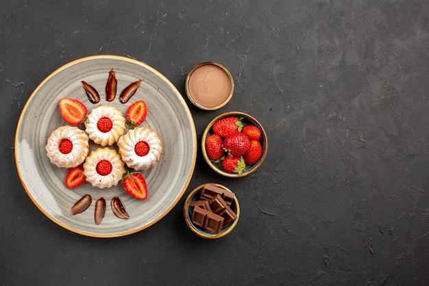 Draufsichtplätzchen und erdbeerplätzchen mit erdbeeren auf weißem teller neben schüsseln mit erdbeerschokolade und schokoladencreme