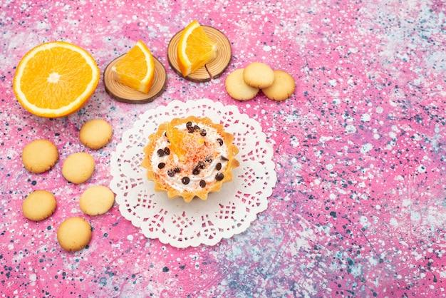 Draufsichtplätzchen und kuchen mit orangenscheiben auf dem farbigen schreibtischplätzchenkeksfruchtkuchen süß