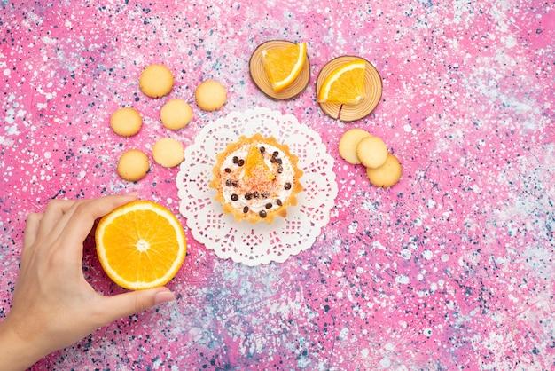 Draufsichtplätzchen und kuchen mit orangenscheiben weiblich, die orange auf dem farbigen oberflächenplätzchenplätzchenfruchtkuchen süß nehmen