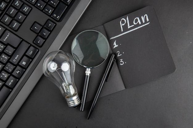 Draufsichtplan auf schwarzem notizblock geschrieben lupa tastatur glühbirne stift auf schwarzem tisch