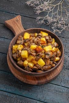 Draufsichtplatte an bord brauner teller mit kartoffeln mit pilzen auf dem schneidebrett auf dem dunklen tisch neben den ästen