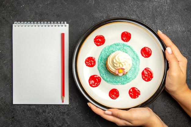 Draufsichtplatte des weißen notizbuchs des kleinen kuchens und des roten bleistifts neben dem kleinen kuchen auf dem weißen teller in den händen auf dem dunklen hintergrund