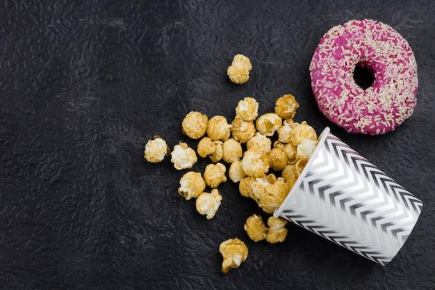 Draufsichtpopcorn und -donut auf einem schwarzen hintergrund