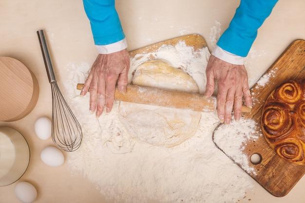 Draufsichtporträt der attraktiven älteren gealterten frau kocht auf küche. großmutter macht leckeres backen.