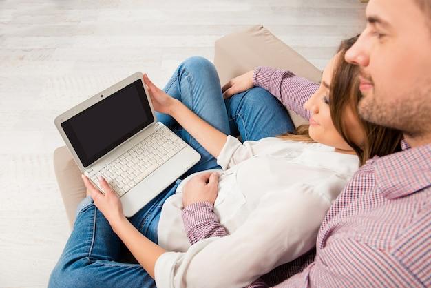 Draufsichtporträt des glücklichen paares, das auf couch mit laptop sitzt