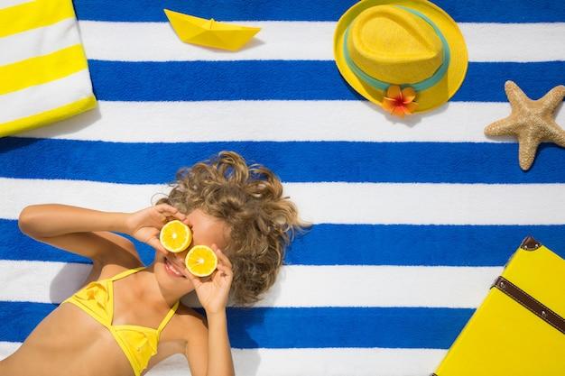 Draufsichtporträt des kindes auf gestreiftem strandtuch sommerferienkonzept