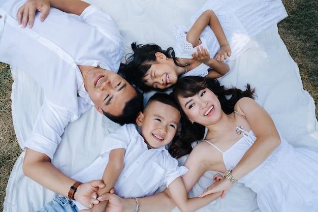 Draufsichtporträt einer fröhlichen asiatischen familie in weißer kleidung, die auf einer decke in einem park liegt und die letzten warmen tage des frühen herbstes genießt.