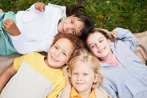 Draufsichtporträt einer verschiedenen gruppe von kindern, die auf gras im park liegen und lächelnd in die kamera schauen