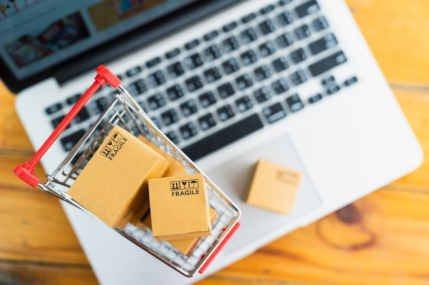 Draufsichtproduktpaketkästen im warenkorb mit laptop-computer für das on-line-einkaufs- und lieferungskonzept