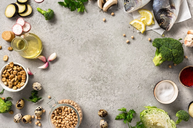 Draufsichtrahmen der rohen kochenden bestandteile für leckeres und gesundes essen. frischer fisch, gemüse und hülsenfrüchte auf grauem hintergrund