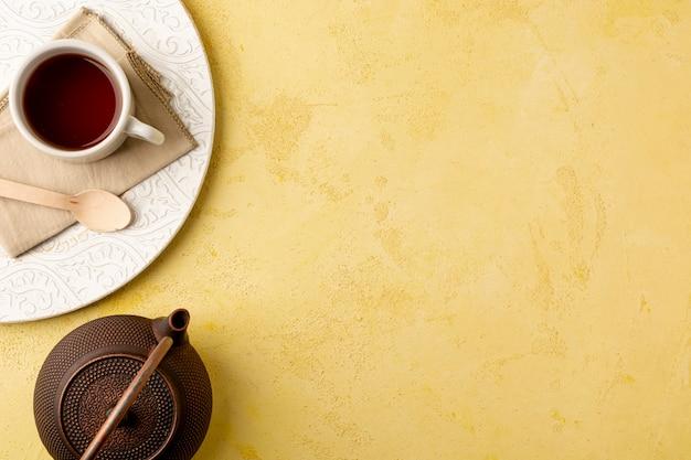 Draufsichtrahmen mit teekanne auf gelbem hintergrund